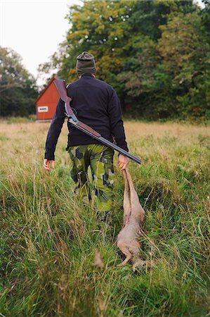 Hunter dragging deer through field Stock Photo - Premium Royalty-Free, Code: 6102-06337050