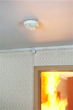 dangerous accident - Home smoke detector, fire in background Stock Photo - Premium Royalty-Free, Code: 6102-06337039