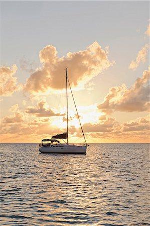 sailboat  ocean - Sailing boat against sunset Stock Photo - Premium Royalty-Free, Code: 6102-06337131