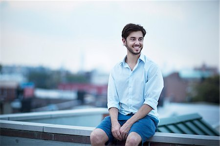 Young smiling man looking away Stock Photo - Premium Royalty-Free, Code: 6102-06471239