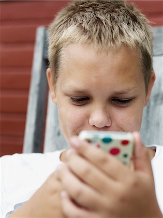 Teenage boy text messaging Stock Photo - Premium Royalty-Free, Code: 6102-06965506