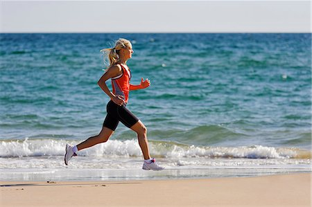 Young woman running on beach, Algarve, Portugal Stock Photo - Premium Royalty-Free, Code: 6102-07158251