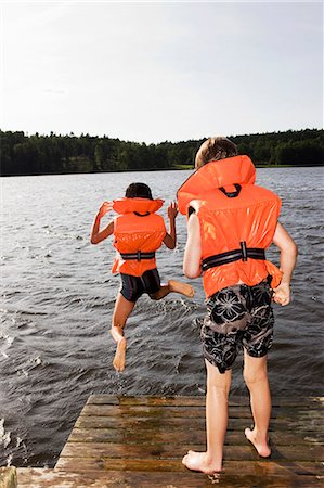Boys jumping into water from jetty Stock Photo - Premium Royalty-Free, Code: 6102-07455732