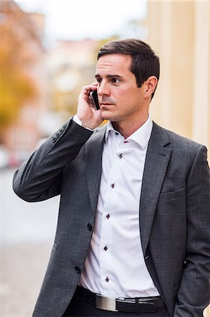 portrait looking away - Mid adult businessman using cell phone, Stockholm, Sweden Stock Photo - Premium Royalty-Free, Code: 6102-07602969