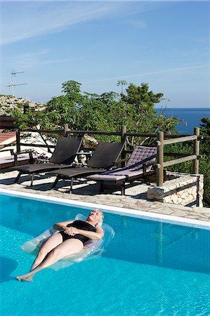 Senior woman in swimming pool, Sicily, Italy Stock Photo - Premium Royalty-Free, Code: 6102-07768764