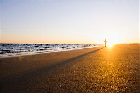 forward - Woman running on beach at sunset Stock Photo - Premium Royalty-Free, Code: 6102-07769357