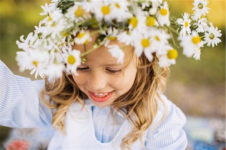 elementary age - Smiling girl with flower wreath Stock Photo - Premium Royalty-Free, Code: 6102-07769471