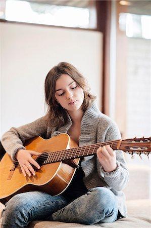 Teenage girl playing guitar Stock Photo - Premium Royalty-Free, Code: 6102-07769400