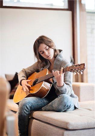 Teenage girl playing guitar Stock Photo - Premium Royalty-Free, Code: 6102-07769401