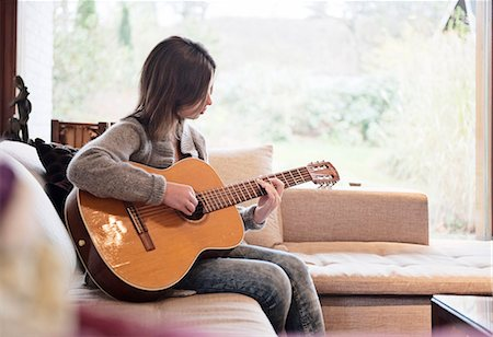 Teenage girl playing guitar Stock Photo - Premium Royalty-Free, Code: 6102-07769402