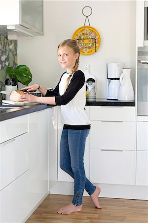 Girl cutting bread in kitchen Stock Photo - Premium Royalty-Free, Code: 6102-07789595