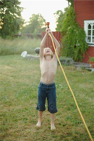 preteen boy shirtless - Boy playing with garden hose in garden Stock Photo - Premium Royalty-Free, Code: 6102-07790055