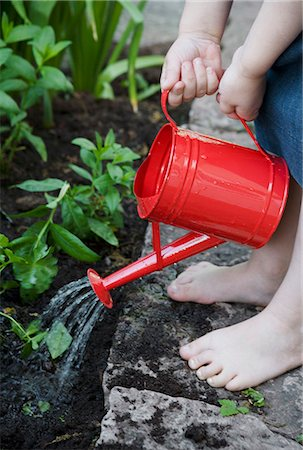Child watering flowers Stock Photo - Premium Royalty-Free, Code: 6102-07790107