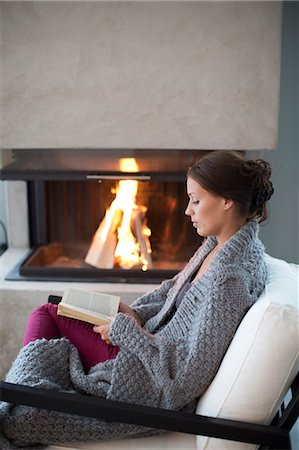 Young woman reading in front of fireplace Stock Photo - Premium Royalty-Free, Code: 6102-07843029