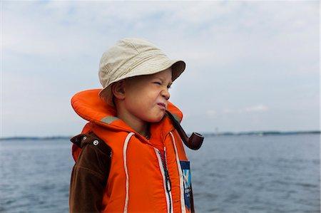 Boy wearing life vest with smoking pipe Stock Photo - Premium Royalty-Free, Code: 6102-07843345