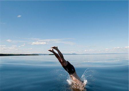Mature man jumping in sea Stock Photo - Premium Royalty-Free, Code: 6102-07843339