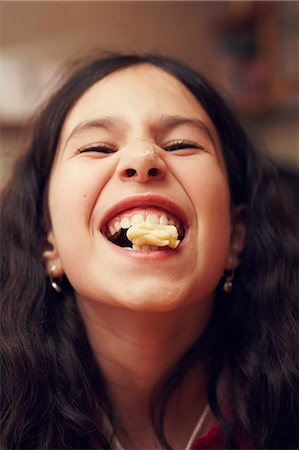 Portrait of smiling girl with cookie in her mouth Stock Photo - Premium Royalty-Free, Code: 6102-07843788