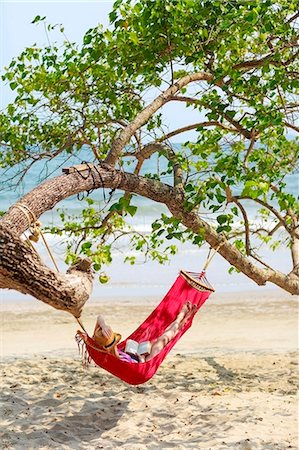 Young woman relaxing in hammock on beach Stock Photo - Premium Royalty-Free, Code: 6102-07843872