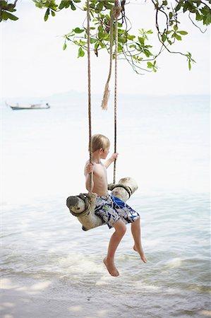 Boy on swing at beach Stock Photo - Premium Royalty-Free, Code: 6102-07843919