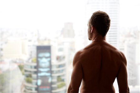 Naked man looking at cityscape Stock Photo - Premium Royalty-Free, Code: 6102-07844042