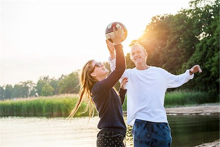 Young couple playing ball at water Stock Photo - Premium Royalty-Free, Code: 6102-07844031