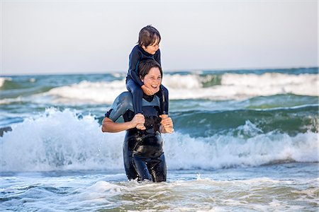 Mother carrying son on shoulders in sea Stock Photo - Premium Royalty-Free, Code: 6102-07844035