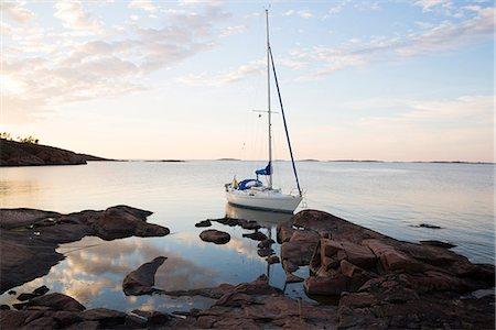 sailboat  ocean - Sailing boat moored at rocky coast Stock Photo - Premium Royalty-Free, Code: 6102-07844247