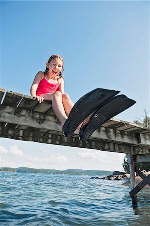 preteen girls bath - Happy girl wearing flippers on jetty Stock Photo - Premium Royalty-Free, Code: 6102-08063042