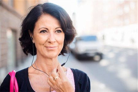 Smiling mature woman with earphones Stock Photo - Premium Royalty-Free, Code: 6102-08063136