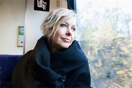 Mature woman looking through window in train Stock Photo - Premium Royalty-Free, Code: 6102-08000527
