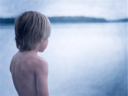 Boy looking at sea, rear view Stock Photo - Premium Royalty-Free, Code: 6102-08000632