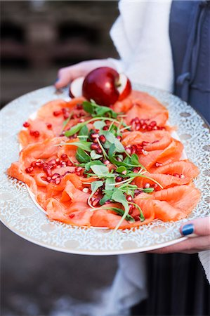 smoked - Person holding tray with smoked salmon and pomegranate seeds Stock Photo - Premium Royalty-Free, Code: 6102-08000708