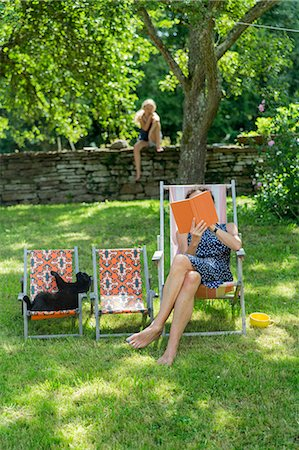 Woman reading book on sun chair Stock Photo - Premium Royalty-Free, Code: 6102-08000910