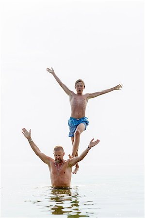 shirtless teen boy - Teenager standing on fathers shoulders in water Stock Photo - Premium Royalty-Free, Code: 6102-08000930