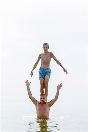 shirtless teen boy - Teenager standing on fathers shoulders in water Stock Photo - Premium Royalty-Free, Code: 6102-08000931