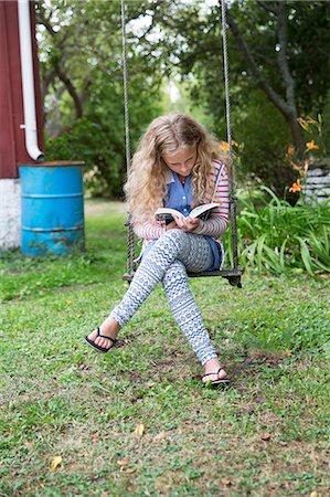 preteen thong - Girl on swing reading book Stock Photo - Premium Royalty-Free, Code: 6102-08001100