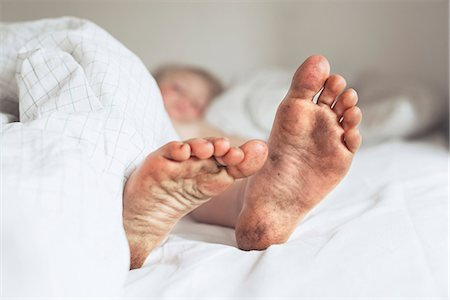 Childs dirty feet in bed Stock Photo - Premium Royalty-Free, Code: 6102-08001449