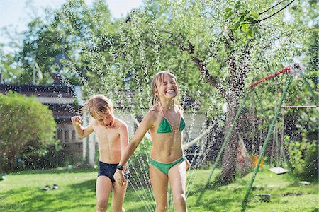 Girl and boy playing with water in garden Stock Photo - Premium Royalty-Free, Code: 6102-08001467