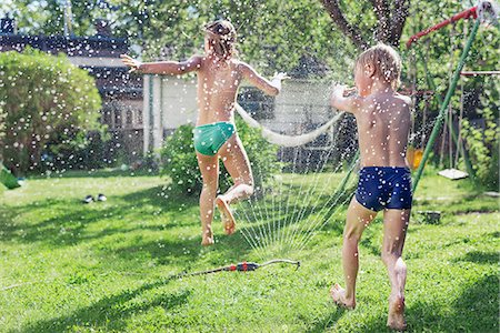 preteen shower pic - Boy and girl playing in garden Stock Photo - Premium Royalty-Free, Code: 6102-08001466