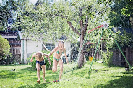Girl and boy playing with water in garden Stock Photo - Premium Royalty-Free, Code: 6102-08001468