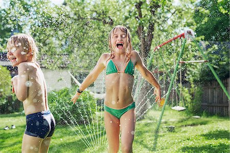 Girl and boy playing with water in garden Stock Photo - Premium Royalty-Free, Code: 6102-08001469