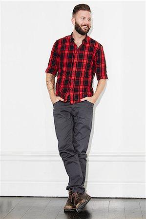 Young man wearing checked shirt, studio shot Stock Photo - Premium Royalty-Free, Code: 6102-08168721