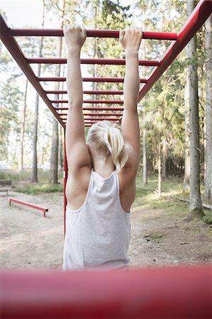 Girl hanging on monkey bars Stock Photo - Premium Royalty-Free, Code: 6102-08120150