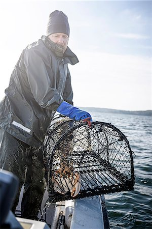 Fisherman with lobster trap Stock Photo - Premium Royalty-Free, Code: 6102-08271148