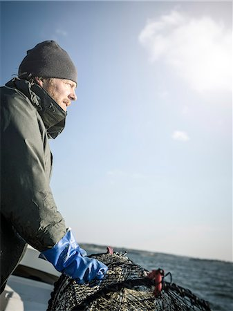 Fisherman with lobster trap Stock Photo - Premium Royalty-Free, Code: 6102-08271149