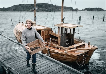 Smiling woman carrying lobsters, boat on background Stock Photo - Premium Royalty-Free, Code: 6102-08271128