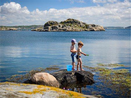 Boys fishing at sea Stock Photo - Premium Royalty-Free, Code: 6102-08271234