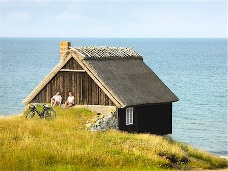 Couple sitting near wooden house at sea Stock Photo - Premium Royalty-Free, Code: 6102-08278907