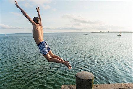 preteen boy shirtless - Boy jumping into water Stock Photo - Premium Royalty-Free, Code: 6102-08384194