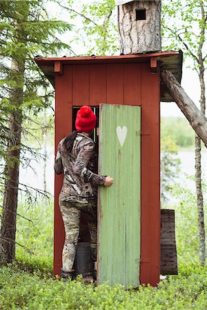 Woman entering wooden outhouse Stock Photo - Premium Royalty-Free, Code: 6102-08384106